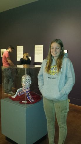 Julia from Germany smiles proudly in front of her work at the Holland Museum in Michigan